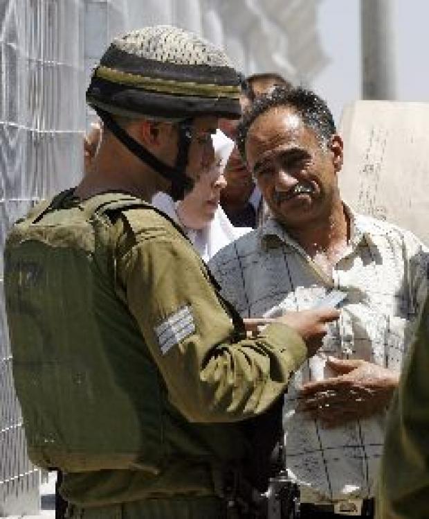 <p>[9963] 5  Soldier checks the identity card of a Palestinian, near Nablus.</p><p>Photo credit: Oleg Popov, © Reuters</p>